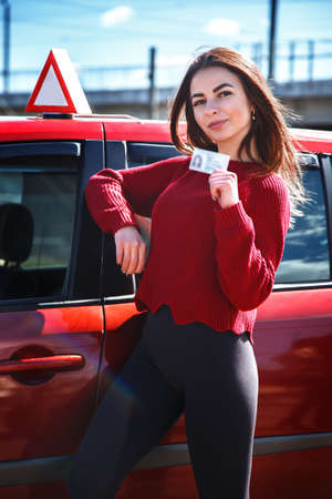 Joyful girl driving a training car with a drivers license card in her hands. Archivio Fotografico