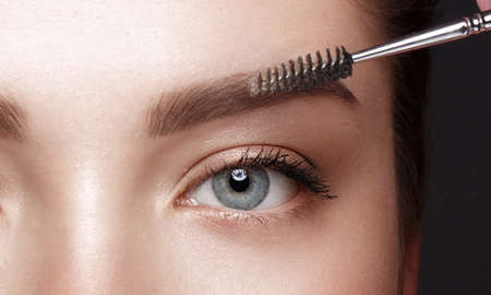 Close-up of female eyes with an eyebrow brush. Eye makeup cosmetics 免版税图像
