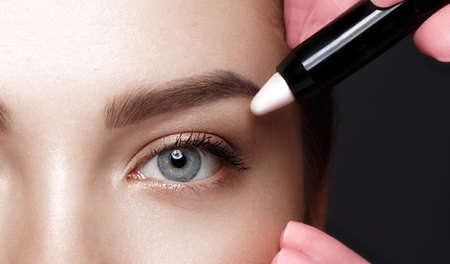 Close-up of female eyes with an eyebrow highlighter. Eye makeup cosmetics 免版税图像
