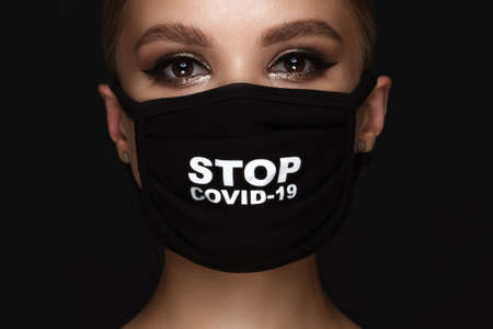 Portrait of a beautiful woman in a black mask stop covid and classic makeup. Mask mode during the covid pandemic.