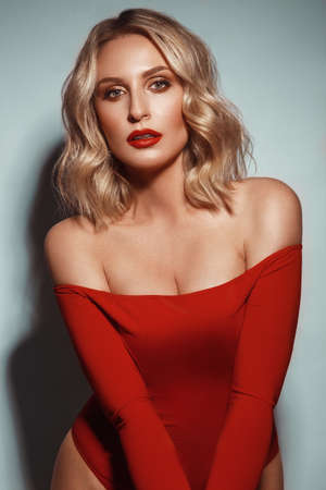 showy sexy blond woman in red clothes, with curls and classic make-up. Beauty face.