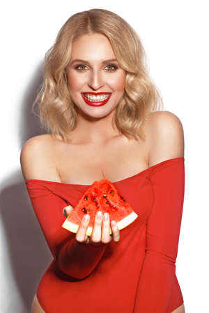 showy sexy blond woman in red clothes, with curls and classic make-up holds a watermelon in her hands. Beauty face. Banque d'images