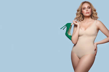 Sexy beautiful blonde plus size model in lingerie bodysuit on a blue background with green shoes in her hands.