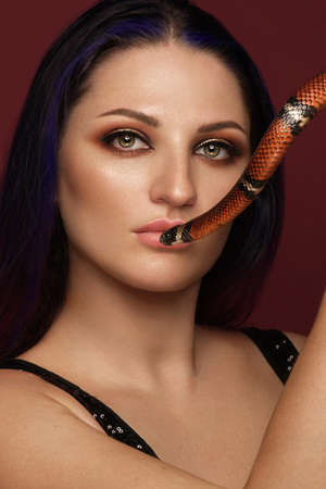 Beautiful girl brunette model with evening fashion make-up with a snake in her hands. Beauty face. Banque d'images