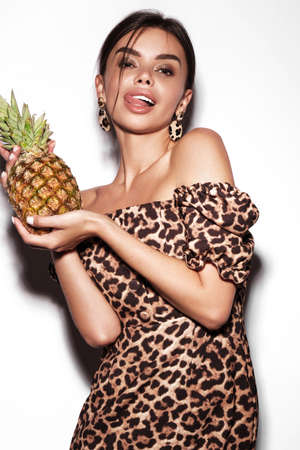 Beautiful sexy woman with pineapple in hands in a leopard dress and earrings, with classic smokey makeup and a fashionable hairstyle. Beauty face.