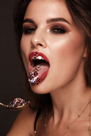 Beautiful girl with red lips and classic makeup and curls with creative glitter. Beauty face