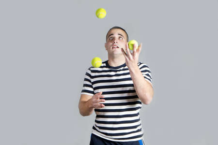 Young juggling tennis balls on grey background