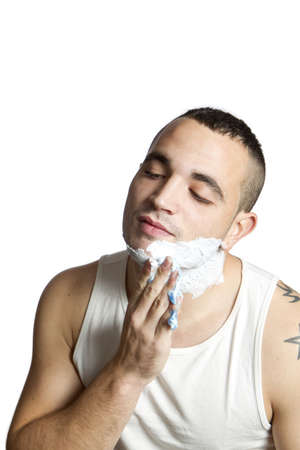 young man giving himself shaving cream on white background