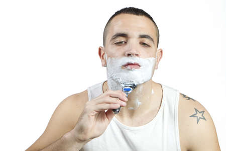 Young man shaving his beard with razor and foam