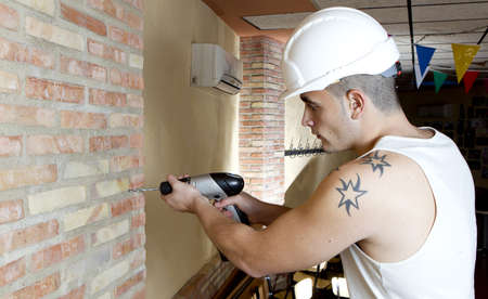 young worker making a hole in the wall with a drill