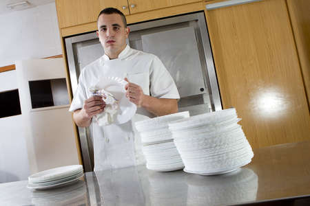 Young tired kitchen assistant dry dishes