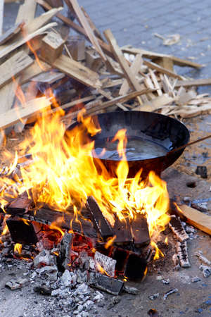 pan with sunflower oil on the fire in a wood fire