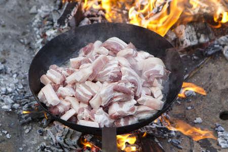saucepan of bacon frying in fire