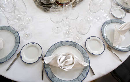 table mounted circular restaurant with covered dishes and glasss Stock Photo