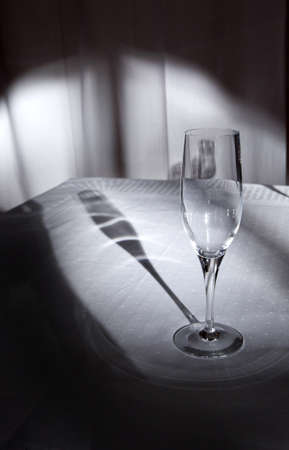 glass of champagne on a tablecloth with shadow