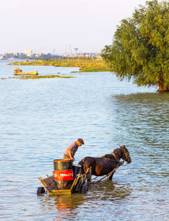 horse drawn: Man on a horse cart with a big container on Danube river Editorial