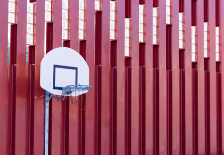 worn structure red: Basketball hoop on red metallic wall structure