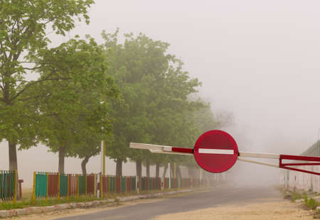 no entry: Barrier with no entry traffic sign on road in fog Stock Photo