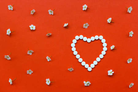white pills: Heart shape made of white pills with white flowers pattern on orange background.Useful as background for medicine, pharmacy, prescription, homeopathy Stock Photo