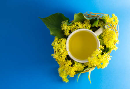 lime blossom: Cup of tea in braided wicker basket filled with lime blossom Stock Photo