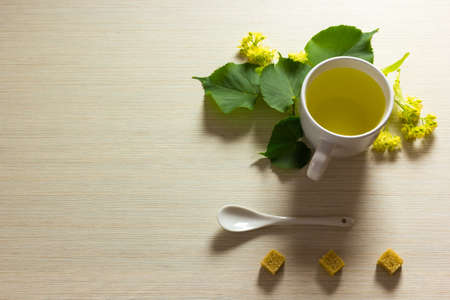 Linden tea cup with linden flowers on textured background photo