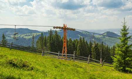 chairlift: Empty chairlift in ski resort with green grass and blue sky