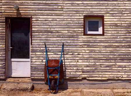 leaning against: Rusty old wheelbarrow leaning against wall Stock Photo