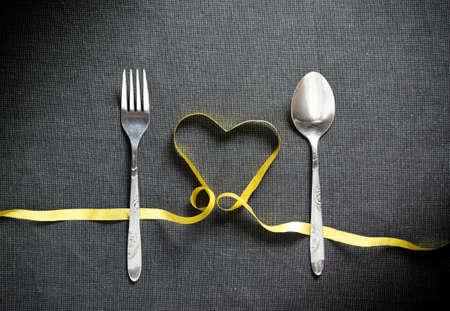 黒い織り目加工の背景に黄色のリボンから作られたハート型にスプーンとフォーク