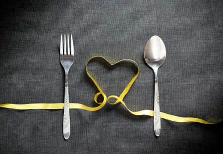 servings: Fork and spoon with heart shape made from yellow ribbon on black textured background