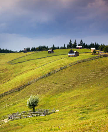 traditional house: Country scene with wooden huts on the hill and sky rain