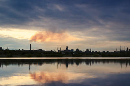 smoldering: Chimney smoldering mirroring in water with rain clouds Stock Photo