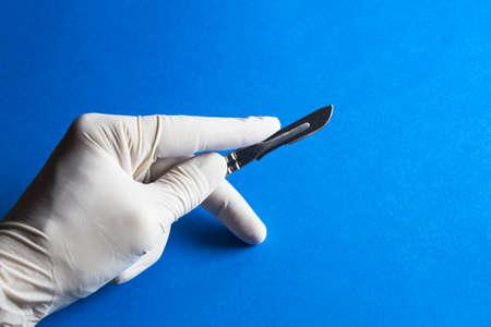 Medische scalpel in een hand met rubberen handschoen Stockfoto
