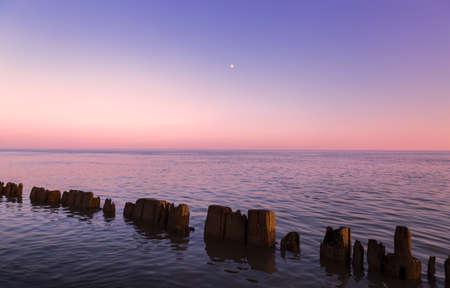 horizonte: Pilares en el agua a la puesta del sol Foto de archivo