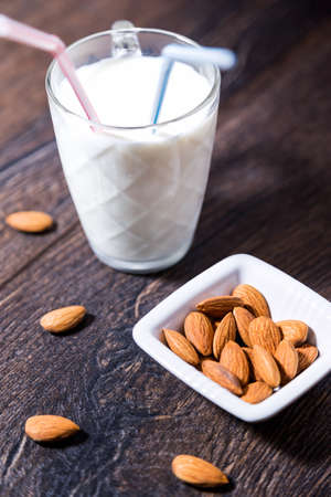 tomando leche: Cup of almond milk with drinking straws and nuts on table