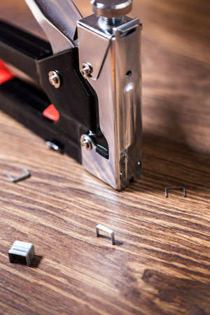 staple gun: Close up carpentry stapler with staples on wood background Stock Photo
