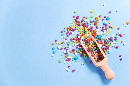Houten scoop met gekleurde suiker goed op, kleurrijke eetbaar suiker parels