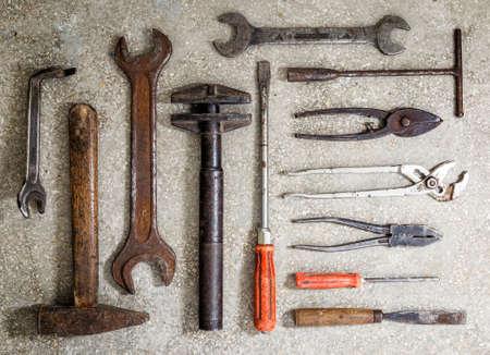 alicates: Viejas herramientas oxidadas dispuestas en el suelo Foto de archivo