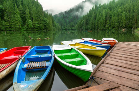 Colorful boats moored on a mountain lake Stock Photo