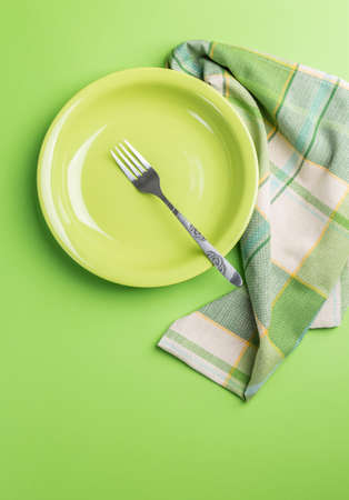 Green plate with fork and napkin on green background above view Stock Photo