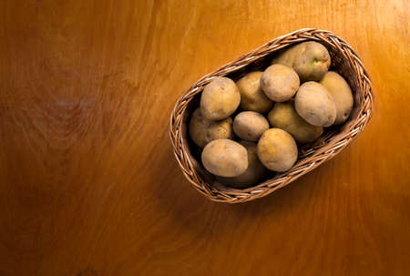 wooden basket: Potatoes in wicker basket on the wooden countertop Stock Photo