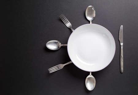 plato de comida: plato blanco con cubiertos sobre background.Useful negro como fondo para la comida, el menú del restaurante u otro