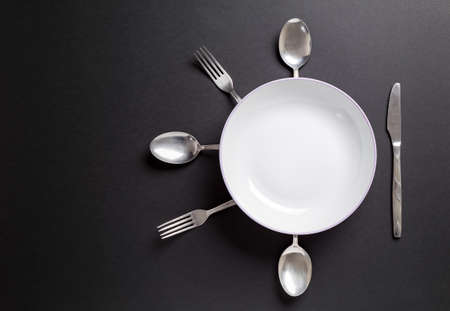 White plate with cutlery over black background.Useful as background for food, restaurant menu or other