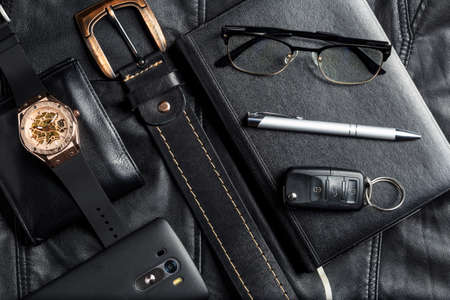 Men's accessories with wallet belt pen car keys glasses smartphone agenda and watch on black leather background. Zdjęcie Seryjne