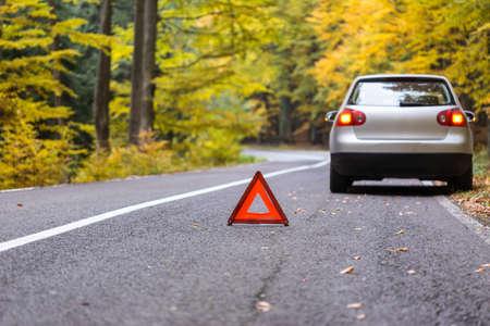 Rode driehoek van een auto op de weg. Gebroken auto in bosschadeauto met weerspiegelende driehoek
