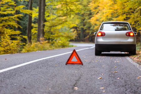 Red triangle of a car on the road.Broken car in forest.damage car with reflective triangle Archivio Fotografico