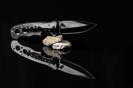 Folding hunting knife on stones mirroring on black background.Useful for adventure, military, hunting, outdoor, protection, security, background presentation Stock Photo