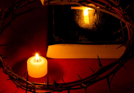 Crown of Thorns of Jesus Christ put on the Bible beside a candle on a red background. Reklamní fotografie