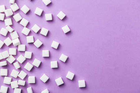 White sugar cubes on magenta background. Useful for a sweet food background presentation.