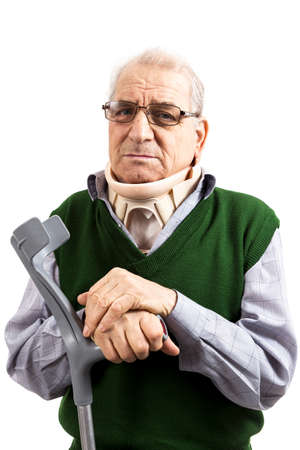 Old man with a surgical cervical collar supporting in a walking stick looking at the camera on white background Stockfoto