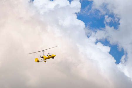 Small helicopter for two person flying on the cloudy sky Banco de Imagens - 102672238